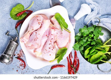 raw chicken legs with fresh spinach and spices