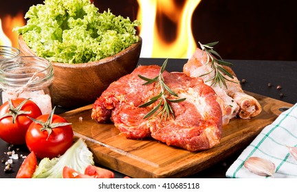 Raw chicken legs on a black stone with fire background