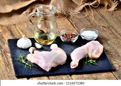Raw chicken legs on a cutting board with a fresh rosemary, garlic, cumin, jug with oil, pepper and salt on a wooden table