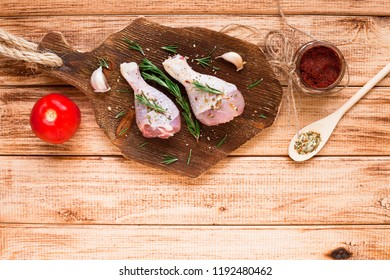 Raw chicken legs with spices, vegetables and rosemary on the dark wooden cutting board. Recipes, healthy food, lifestyle concept. Top view. Close up.