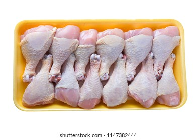 Raw chicken legs in yellow plastic tray isolated on white background