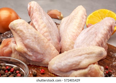 raw chicken with lemon on a wooden board