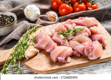 Raw chicken meat fillet cut into cubes on cutting board. White background. Top view