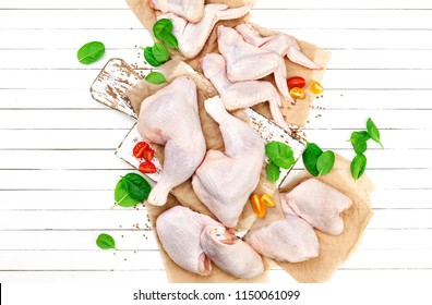 Raw chicken meat on cutting board on white wooden background. Top view