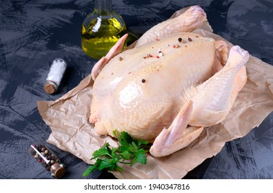 Raw chicken meat on parchment paper, sea salt, pepper, parsley and cooking oil on the gray table. Cooking poultry