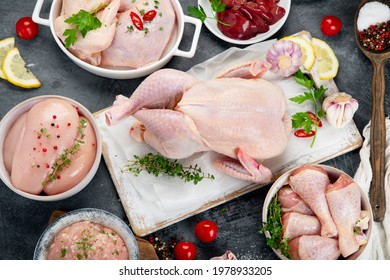 Raw chicken meat parts with spices and herbs for cooking on dark background. Top view, copy space