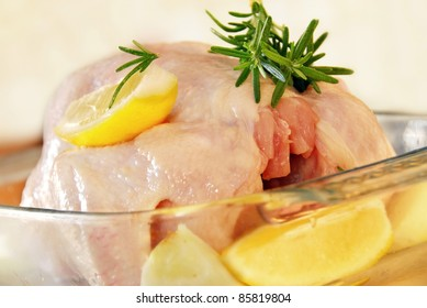 raw chicken meat with rosemary and lemon ready to bake