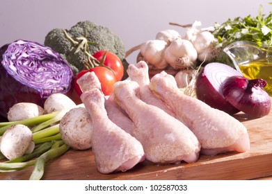 Raw Chicken on chopping board with vegetables