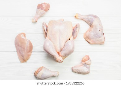 Raw chicken and chicken parts (Breast, wings and legs) Top view on wooden background.