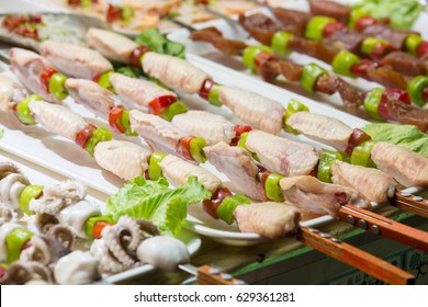 Raw chicken with pepper on skewer on white plate