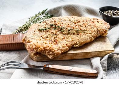 Raw chicken schnitzel in breadcrumbs. Gray background. Top view