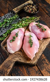 Raw Chicken skinless thigh fillet on a wooden cutting board. Black background. Top view.
