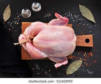 Raw chicken with spices on a wooden board on a black stone.