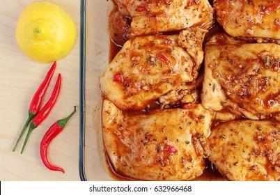 Raw chicken thighs marinating