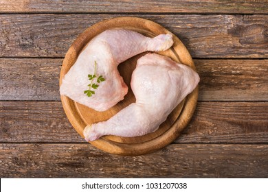 Raw chicken thighs on a round wooden cutting board on a wooden background.Top view