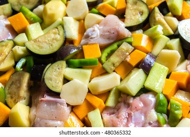 raw chicken with vegetables in pan