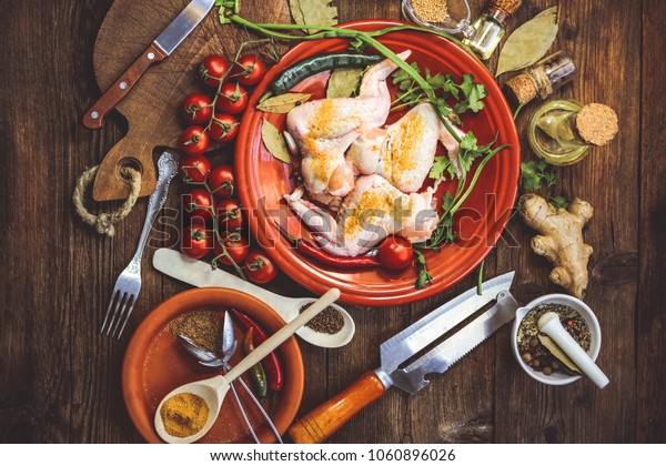 raw chicken wings and other food ingredients on a wooden background.