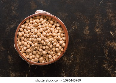 Raw chickpeas in a ceramic bowl on a dark background. A view from above, a copy of space