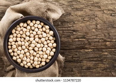 Raw chickpeas or garbanzo beans (lat. Cicer arietinum) in rustic bowl, photographed overhead on rustic wood with copy space on the side (Selective Focus, Focus on the chickpeas)