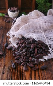 Raw chocolate beans in sack on wooden table