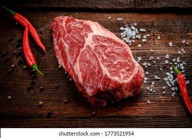 Raw Chuck Eye Roll beef Steak on a rustic wooden background with seasonings