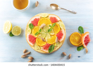 Raw citrus cake with grapefruit, orange, lime and lemon with nuts and mint. Healthy fresh summer dessert. Gluten free, no baking vegan food