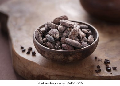 Raw cocoa beans in a wooden bowl