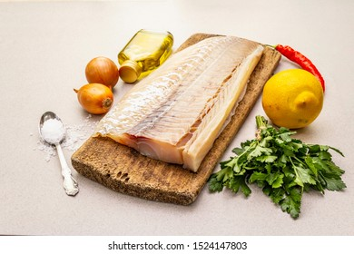 Raw cod loin fillet with vegetables, spice, olive oil and salt. Freshly thawed fish, healthy vegetarian food concept. Old wooden cutting board, stone concrete background close up