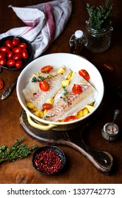 raw codfish fillet with potatoes and tomatoes in ceramic baking dish