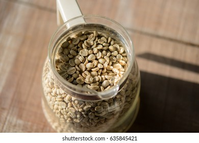 Raw coffee bean in a glass jar on wooden table