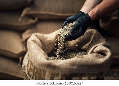 raw coffee pouring from a handful in a bag, against the background of a warehouse, closeup side view