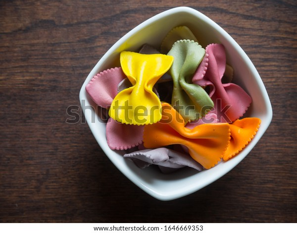 Raw colorful pasta in a white bowl standing on a wooden table