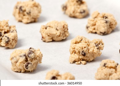 Raw cookie dough on a baking sheet with parchment