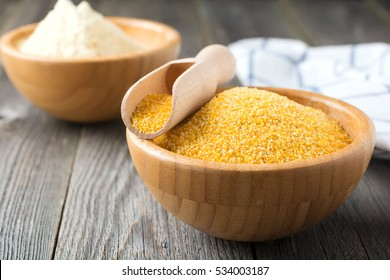 Raw corn grits polenta in a bamboo bowl on the old wooden background. Selective focus.
