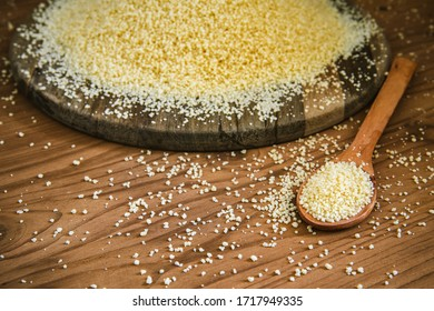 Raw couscous in fall on rustic wooden table.