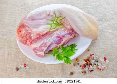 raw cow tongue with greenery and dry different peppers on burlap background, close up