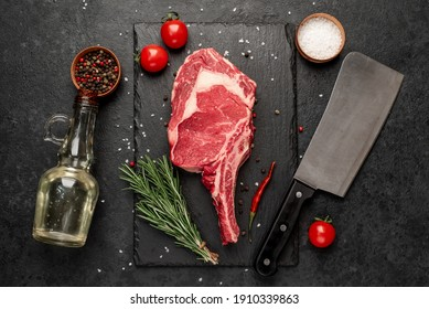 Raw cowboy steak with spices on stone background