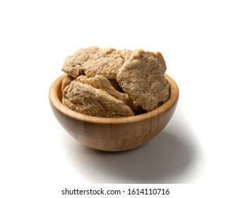Raw dehydrated soy meat or soya chunks in wood bowl isolated on white background. Texturized vegetable protein, also known as textured soy protein or TSP