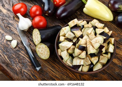 raw diced eggplant in a bowl, tomato and garlic, detail of a cut raw vegetables, vegetarian food, healthy life