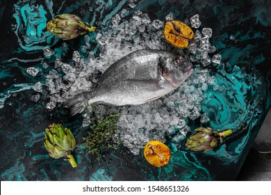 Raw dorada fish with ingredients on dark background