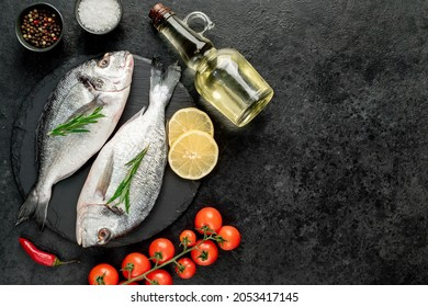 raw dorado fish with lemon and rosemary on stone background with copy space for your text