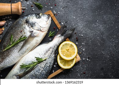 Raw dorado fish on black stone table with ingredients for cooking. Top view with copy space.