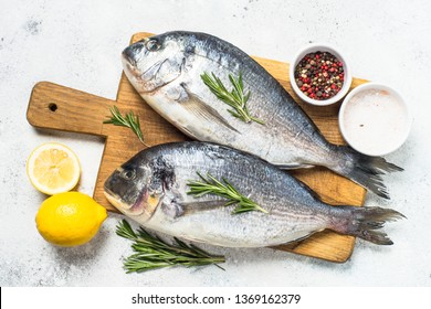 Raw dorado fish on cutting board on white table with ingredients for cooking. Top view with copy space.