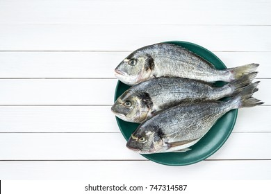 Raw dorado fish on green plate on white wooden table. Top view, copy space