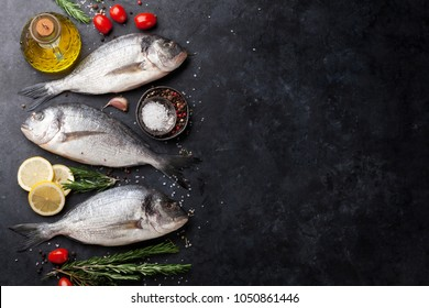 Raw dorado fish with spices cooking on cutting board. Top view with space for your text