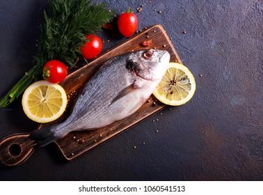 Raw dorado fish with spices on dark background, top view
