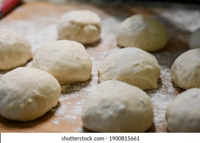 Raw dough balls and flour on wooden counter. Preparation for cooking pastries.