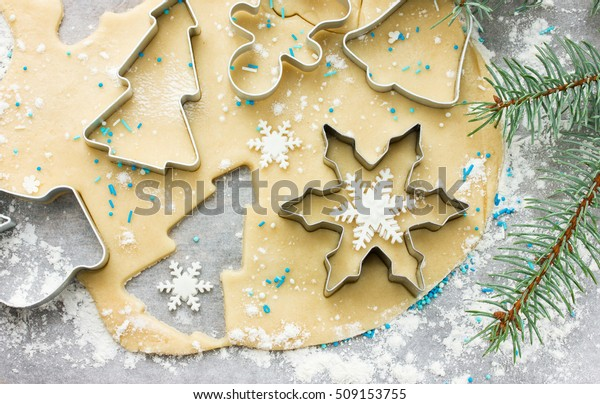 Raw dough for Christmas cookies and cookie cutters shaped glove, Christmas tree, snowflake, jingle bell, gingerbread man