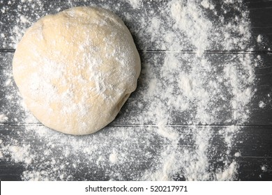 Raw dough for pizza with flour on wooden table