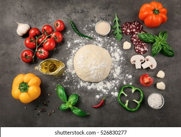 Raw dough for pizza with ingredients and spices on table
